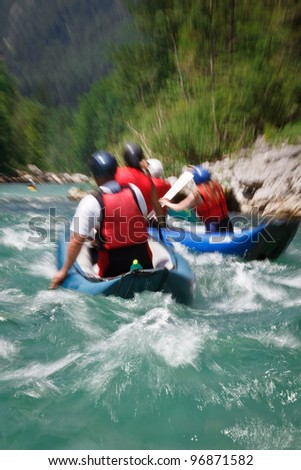 white water rafting (motion blur is used to convey rapid flow of the river/movement of the raft boat)