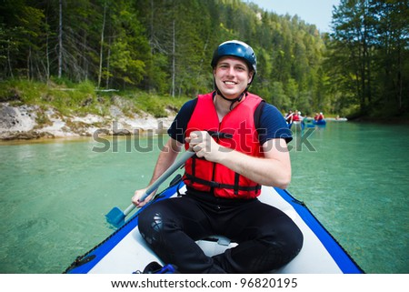 white water rafting - young man in a raft boat,  paddling, smiling - stock photo