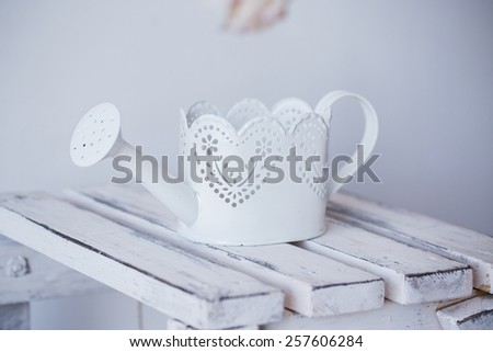 White watering can on desk - stock photo