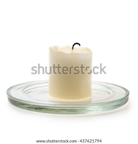 White wax candle on a glass stand. The calcine thick with charred candle wick stands on a glass stand. Isolated on white background - stock photo