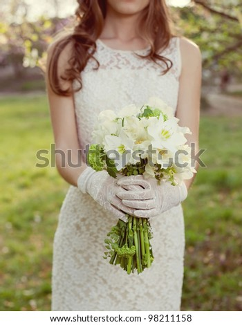 white wedding bouquet in the hands of the bride - stock photo
