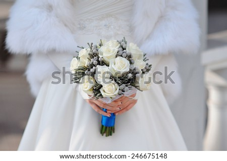 white wedding bouquet of roses in hands of the bride. - stock photo