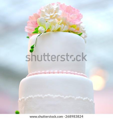 White wedding cake decorated with cream flowers close up photo - stock photo