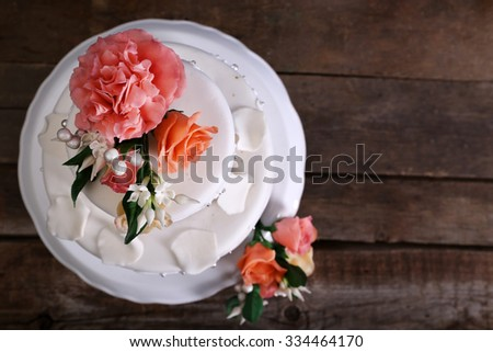 White wedding cake decorated with flowers on wooden background - stock photo