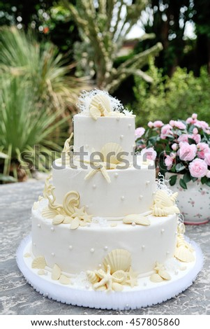 White wedding cake decorated with marzipan shell and starfish