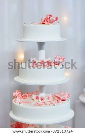 White wedding cake decorated with pink sugar flowers - stock photo