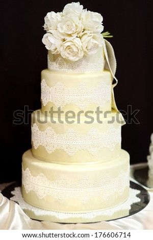 White wedding cake decorated with white lace and flowers - stock photo