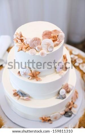 White Wedding Cake with Beach Decor - stock photo