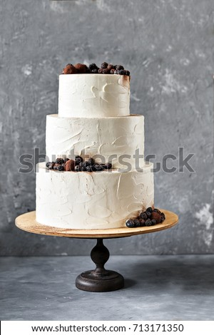 White Wedding Cake With Blackberries Blueberries And Chocolate Truffles On A Grey Background Selective