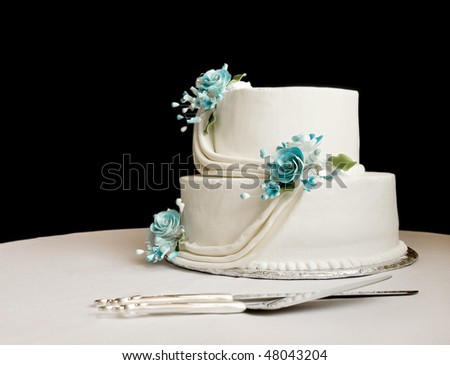 white wedding cake with blue flowers on a table with a black background - stock photo