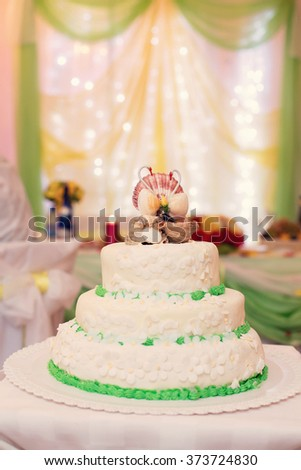 white wedding cake with green details and cockleshells