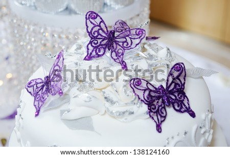 White wedding cake with purple butterfly decoration