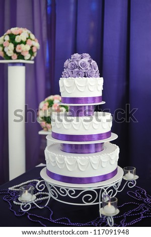 White wedding cake with purple flower detail - stock photo