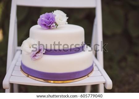 White wedding cake purple flowers decoration stock photo royalty white wedding cake with purple flowers decoration outdoors on wooden modern chair front view mightylinksfo
