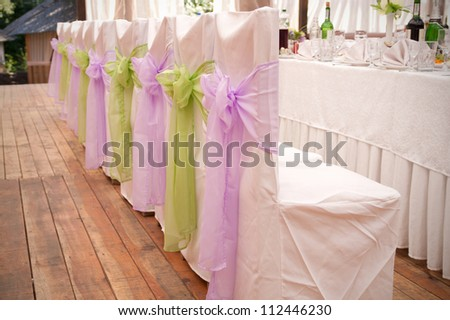 White wedding chairs with silk ribbons - stock photo