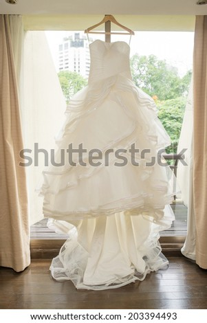 White Wedding dress hanging on a shoulders