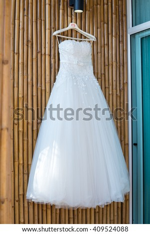 White Wedding dress hanging on bamboo wall awaiting  wedding ceremony party outdoors - stock photo