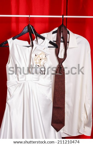 White wedding dress hanging on the rack next to the groom shirt and tie - stock photo