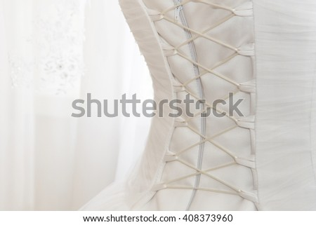 White wedding dress with lacing on the back on a white background. Wedding dress back detail, close up, copy space - stock photo