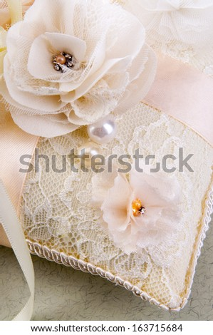 White wedding small satin pillow with flowers for rings on gray background - stock photo