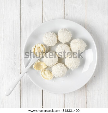White whole and broken coconut candy balls in plate on white rustic wooden background. Top view point. - stock photo
