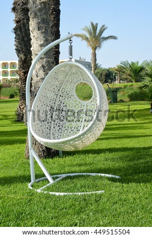 White wicker hammock for relaxing on green grass - stock photo