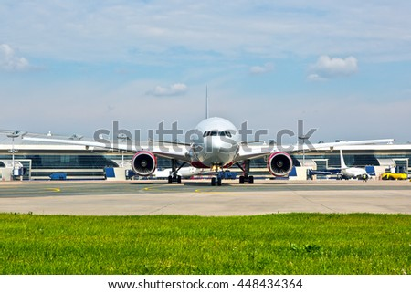 White wide-body passenger airplane moving on the airport tarmac. Front view of aircraft. - stock photo