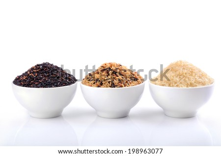 White, wild and brown rice in ceramic bowls on white background