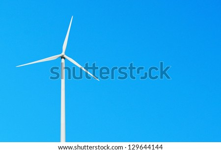 white wind turbine against a vibrant blue sky (copy-space for your design) - stock photo
