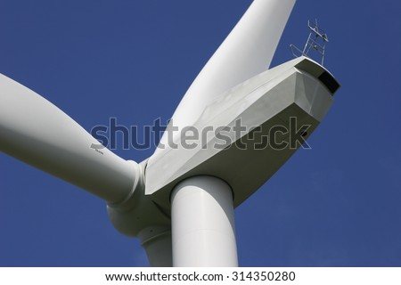 White wind turbine against dark blue sky facing to the left and angled. Rear view with the generator housing and a small section of the blades visible - stock photo