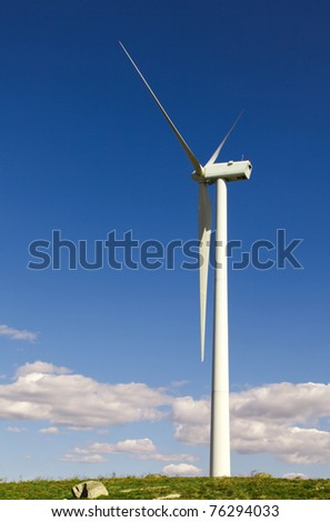 White wind turbine generating electricity on blue sky - stock photo