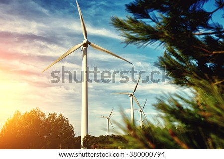 White wind turbine located outside the city, electric generator against beautiful cloudy sky and sunset, alternative energy resources, windmill in field at evening  - stock photo