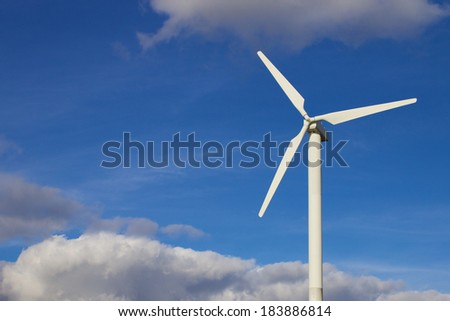 White wind turbine standing in front of a bright summer sky - stock photo