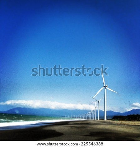White wind turbines stand neatly in a row. - stock photo