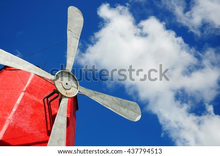 White windmill metal vanes against clouds and blue sky background
