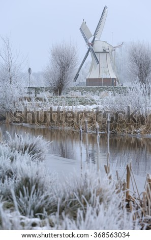 White windmill (Witte Molen) in the frozen, Dutch landscape on a winter day. Shallow D.O.F. - stock photo