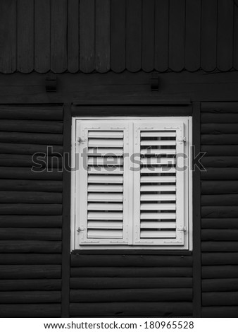 White window on black wooden house - stock photo