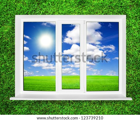 White window on green grass with view on summer field