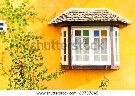 White window on yellow wall - stock photo