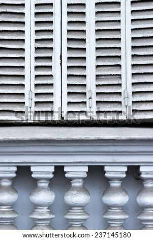 White window shutter over dusty deco architecture pillars - stock photo