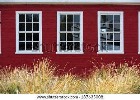 White windows contrast against red walls and golden dune grass - stock photo