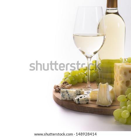 White wine and cheese platter and grapes - stock photo