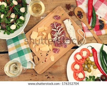white wine and different snacks on wooden table - stock photo