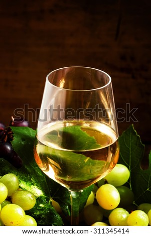 White wine and green grapes in a wicker basket in a wine cellar, selective focus