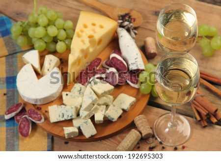 white wine and snacks on wooden table