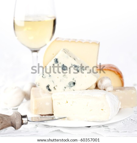 White wine and Various types of cheese on a plate - stock photo