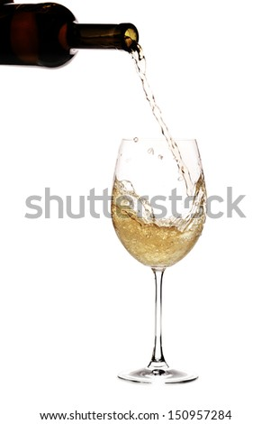 White wine being poured into a glass out of a bottle