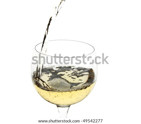 White wine being poured into a glass over white