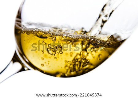 White wine being poured into a wineglass, isolated  on white background - stock photo