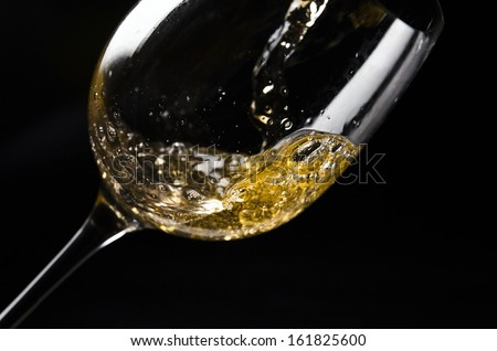 White wine being poured into a wineglass on black background